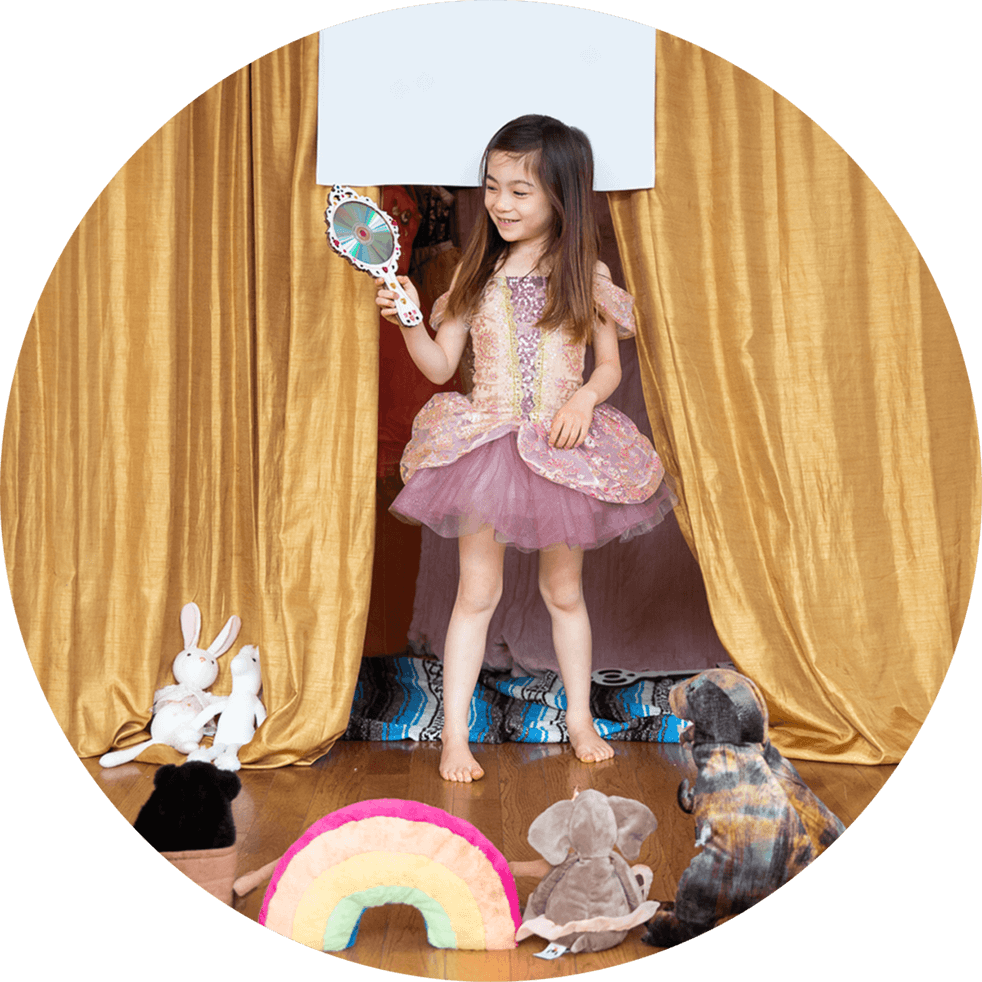Child on a stage playing dress-up. There are gold curtains behind her and an audience of stuffed animals on the floor in front of her.
