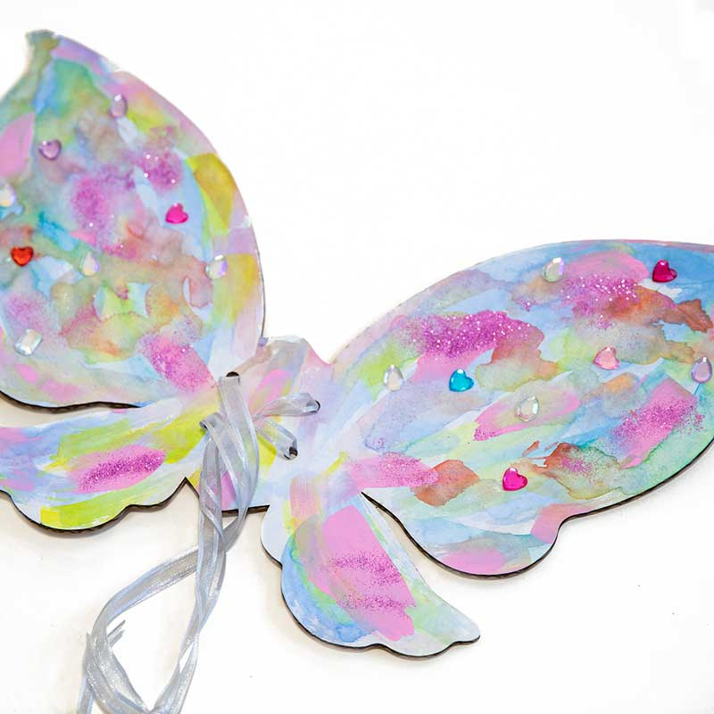 Close up of completed fairy wings craft project. Cardboard fairy wings are decorated with pastel colored paint, pink glitter, and sparkly gems.