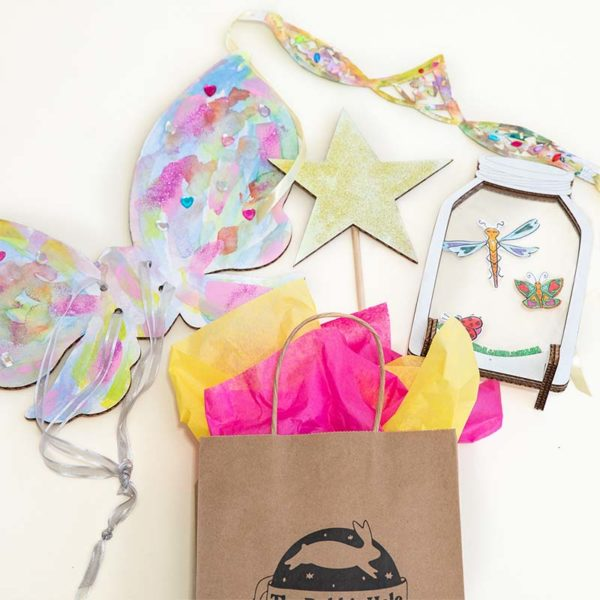 Contents of Fairy Magic birthday party in a box craft kit, including a star-shaped wand, cardboard bug jar and fairy wings, and paper crown.